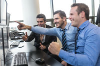 Successful business team celebrates business success in modern corporate trading office.