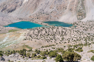 The beautiful mountain trekking road with clear blue sky and rocky hills and fresh mountain lake in Fann mountains in Tajikistan