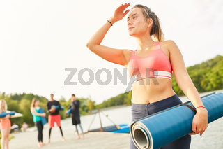 Junge Frau im Wellness Urlaub mit Yogamatte
