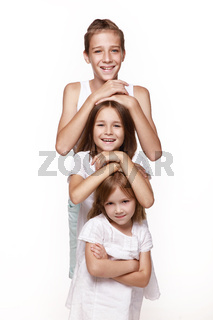 Three children in the studio on a white background, a brother and two sisters laugh