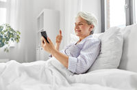 senior woman with phone having video call in bed