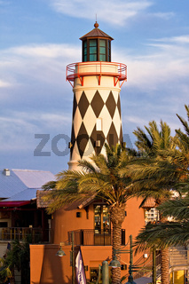old lighthouse over blue sky and palm trees