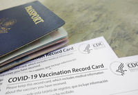 US passport with COVID-19 Vaccination Record Cards, issued by the United States CDC to indicate an individial has been vaccinated against the Coronavirus