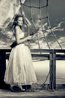 Beautiful girl in white dress on deck of the saili