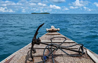 Bow of old wooden boat approaching tropical island