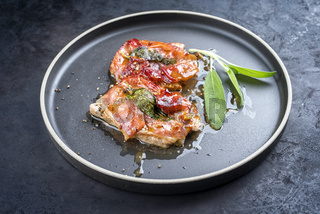 Modern style traditional Italian fried pork saltimbocca alla Romana with Parma ham and sage leaves offered as close-up in a Nordic design plate