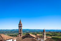Piedmont hills in Italy with scenic countryside, vineyard field and blue sky. Govone bell tower on the left.