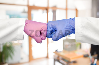 hands of doctors in gloves make fist bump gesture
