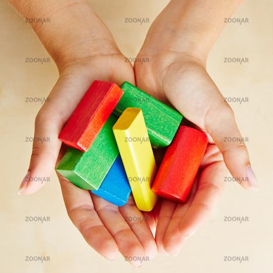 Hände von oben halten Bausteine