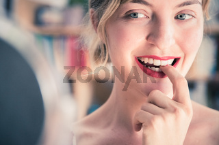 Attractive red lip stick and healthy white teeth: Blonde young woman with colorful nail polish is looking herself in the mirror.