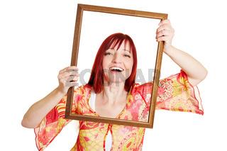 Frau hält leeren Rahmen vors Gesicht
