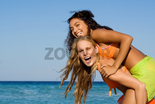 diversity, mixed race friends playing piggyback on summer holiday at beach