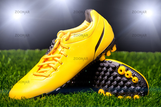 Football boots on the grass in the stadium floodlights.