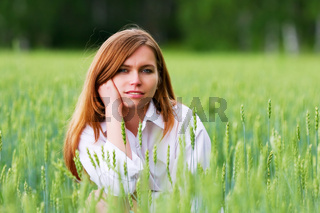 Young woman sitting in a grass