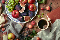 Dish with figs, apples and grapes and cup of coffee on wooden background with warm sweater, scarf, autumn leaves and apples. Autumn background, top view.