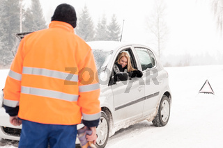 Man helping woman car breakdown assistance snow