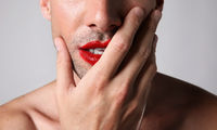 Cropped portrait of young caucasian man with red lips. Isolated on white wall.