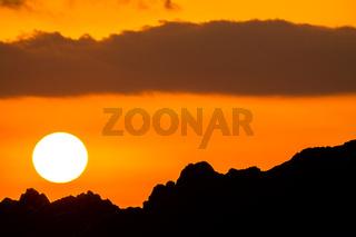 Sun in Orange Sky and Silhouette of Mountain Range