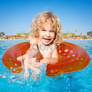 Happy child playing in blue water