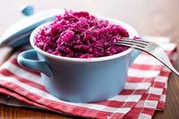 Red sauerkraut. Sour pickled cabbage in blue pot.