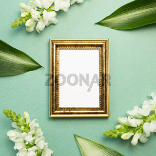 Empty picture frame and white flowers on green background. flat lay, top view, copy space