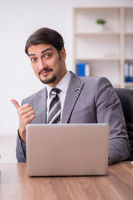 Young attractive male employee sitting at workplace
