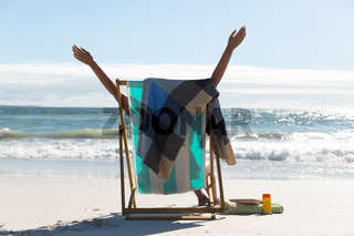 Mixed race woman on beach holiday sitting in deckchair stretching