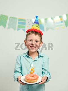 Birthday donut with candle in boy hands