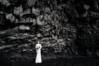 Destination Iceland wedding. The bride in a white silk dress with a bouquet in her hands, stands on black sand, on the beach of Vik, under a rocky mountain of basalt stones.