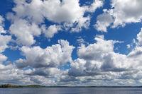 Blauer Himmel mit weißen bis grauen Wolken über dem Plöner See in Schleswig-Holstein.