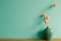 Vase of pink dry flowers on wooden table. mint wall background. home interior