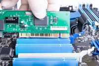 expert in white mitten is installing green PCI LAN or video card into blue computer slot