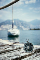 Sailing: nautical compass on wooden dock pier. Sailing boats in the background.
