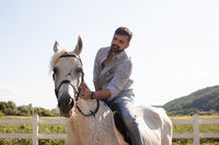 The handsome man rides a horse on a ranch