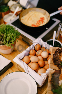 Chicken eggs, on the table in the kitchen with plates, a flower pot and a frying pan.