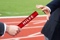 Businessmen pass help baton in German Hilfe relay race in stadium