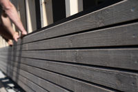 A slective focus view of two construction workers add wooden siding while building a garage