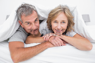 Happy couple under the duvet