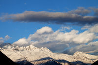 High snowy winter mountains in sunlight clouds at sunny evening