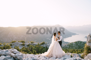 A wedding couple stands on top of a mountain with panoramic views of the Bay of Kotor, at sunset. The groom gently hugs the bride. Fine-art destination wedding photo in Montenegro, Mount Lovchen.