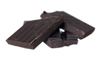 Pile of dark chocolate chunks on white background. Focus on front left.