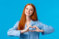 Relationship, love and tenderness concept. Cute sensual and feminine redhead girl long hair, wearing nightwear, showing heart gesture and smiling, showing affection or like, blue background
