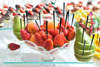 Exquisite dessert table with fruit and sweets. Red strawberry, green pear, citrus on the table. Professional and exquisite сatering service