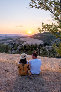couple man and woman on vacation in Toscane Italy, man and woman mid age visiting Toscany region on the golden hills