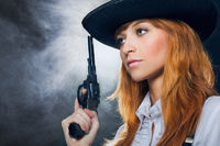 The beautiful girl in a hat, with a revolver.