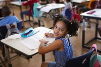 Portrait of african american girl smiling while sitting on her desk in class at elementary school
