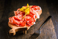 Prosciutto with grilled peppers -  Italian dry ham with grilled green peppers on wooden table
