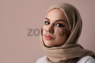 Close-up portrait of young muslim woman wearing beige hijab. Isolated.
