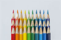 Three rows of colored pencils against a white background