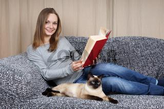 Frau entspannt mit Buch und Katze
